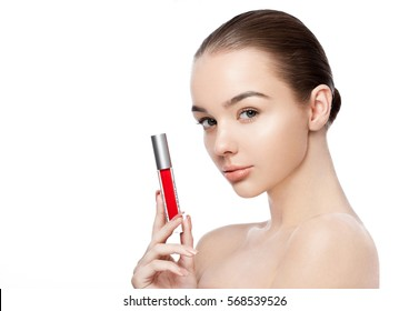 Beautiful girl holding liquid red lipstick container on white background