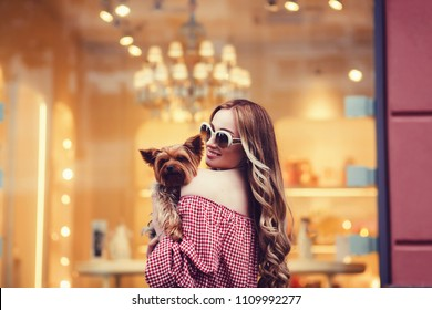 Beautiful girl holding little dog in city