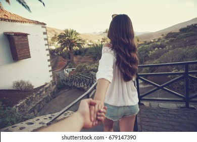 Beautiful girl holding mans hand and leading him. Love and travel concept. Beautiful tropical landscape.