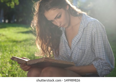 Beautiful girl holding an open book, background summer green park.