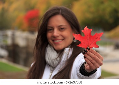 Beautiful girl holding red maple leaf, the symbol of Canada, in a park in autumn, Focus at the red maple leaf, girl blurred. The maple leaf is the most widely recognized national symbol of Canada.