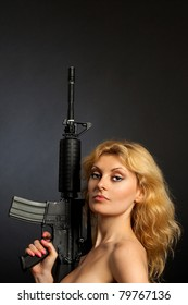 Beautiful girl holding a rifle isolated on a black background