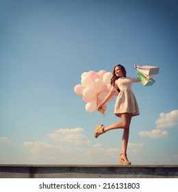 Beautiful girl holding shopping bags and colored balloons over blue sky, toned.