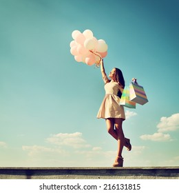 Beautiful girl holding shopping bags and colored balloons over blue sky, toned