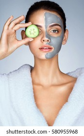 Beautiful girl holding a slice of cucumber in front of her face. Photo of girl in white bathrobe and with mask of clay on face. Grooming himself