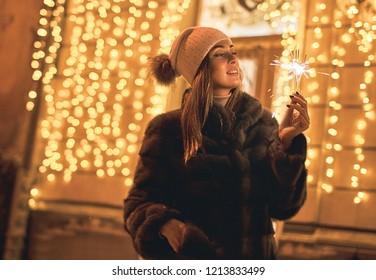 Beautiful girl holding a sparkler enjoys Christmas mood in old European city on festive golden yellow lights bokeh background