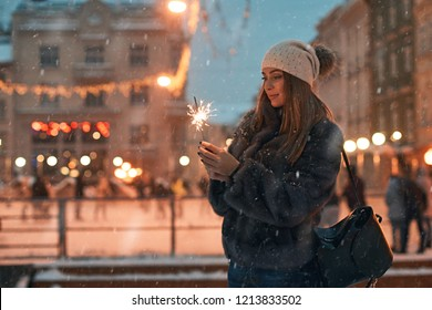 Beautiful girl holding a sparkler enjoys Christmas mood in old European city on outdoor skating rink background with snow and cozy bokeh lights