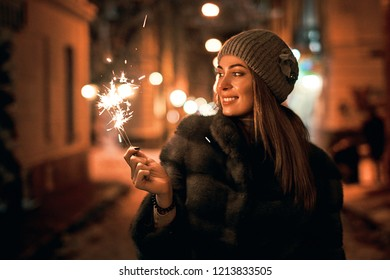 Beautiful girl holding a sparkler smiles and enjoys Christmas mood in old European city on dark background