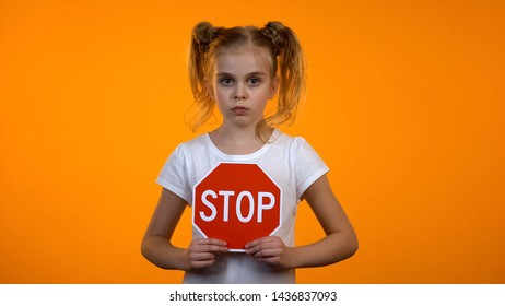 Beautiful girl holding stop sign, family misbehavior, children rights protection