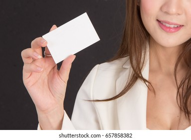 Beautiful girl holding a white business card on a black background.