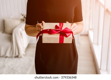 The beautiful girl holds a gift or a surprise in hand