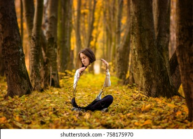 A beautiful girl holds a mirror in which the autumn forest is displayed