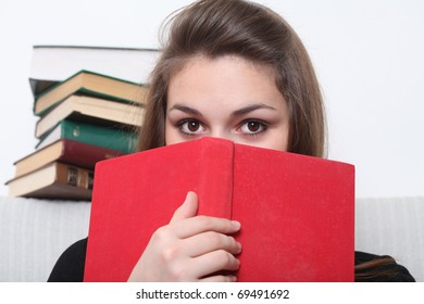 Beautiful girl holds red book before her face. Look into the camera.
