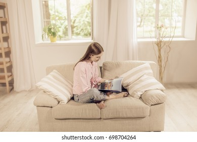 Beautiful girl at home sitting on the couch, reading a magazine. Home concept, pretty young lady on beige sofa, relaxing.