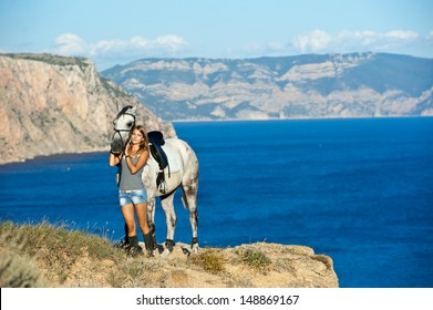 beautiful girl with the horse on the sea shore. Horsewoman