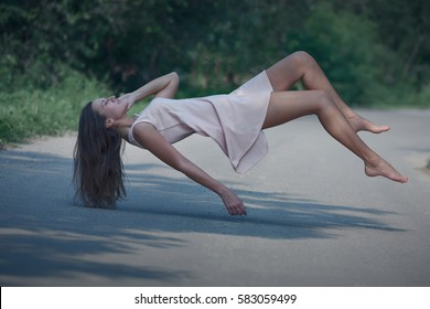 Beautiful girl hovering above the empty road enjoying in levitation.