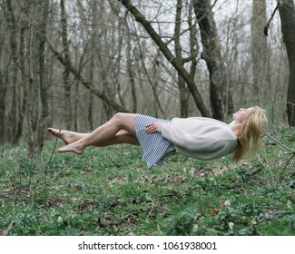 Beautiful girl hovering above the ground enjoying in levitation in forest.