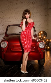 A beautiful girl huddled on the hood of the car. Holds white shoes in his hands. In a dress in pin-up style. Caucasian brunette model in retro fashion and standing at the old car without a roof.