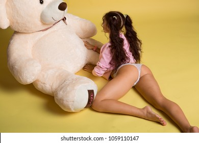 beautiful girl hugging big huge teddy bear soft toy, smiling happily on a yellow background