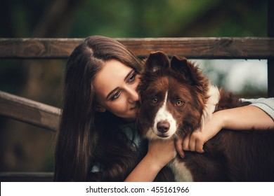 beautiful girl hugging a dog in the park