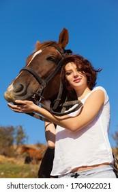 Beautiful girl hugs a horse