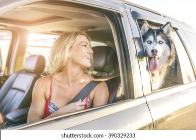 Beautiful girl and husky sitting in a car and looking at camera - Funny dog with owner in a car