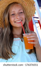 Beautiful girl with an iced drink, straw hat on beach, vertical