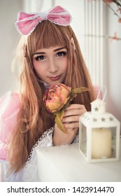 Beautiful girl in the image of a doll in a bright interior. Studio photography . Girl loli in a pink dress.