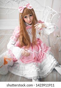 Beautiful girl in the image of a doll sitting on the floor in a bright interior. Studio photography . Girl-loli in a pink dress and white tights. Cosplay, Anime, Harajuku