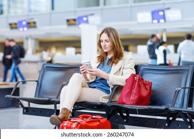Beautiful girl at international airport, reading her ebook computer and drinking coffee to go while waiting for her flight. Female passenger at terminal, indoors. Traveling people