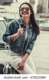 Beautiful girl in jean jacket and sun glasses is looking at camera and smiling while leaning on her car