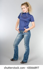 The beautiful girl in jeans and a dark blue vest on a grey background