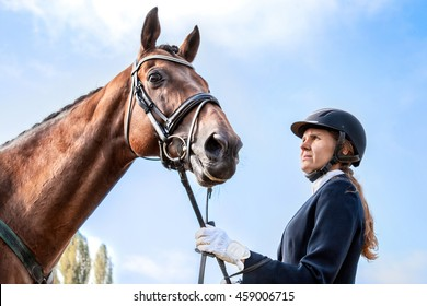 Beautiful girl jockey stand next to her brown horse wearing special uniform on a blue sky background on a sunny day. Equitation sport competition and activity.