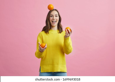 Beautiful girl juggleling with oranges on a colorful background