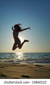 Beautiful girl jumping on a beach