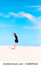 Beautiful girl jumping on the sand dune. Clear blue sky in the background.