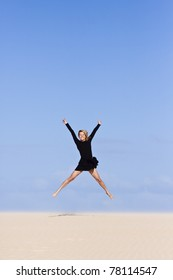 Beautiful girl jumping on the sand  dune.