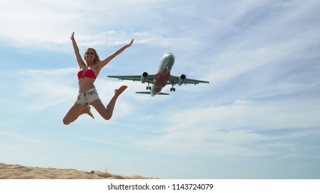A beautiful girl jumps up against the background of a low flying plane. The plane is landing.