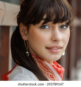 Beautiful girl with kerchief on neck against wooden handrail.