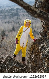 Beautiful girl in kigurumi tiger suit stand on top of the rock, with forest on background