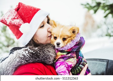 Beautiful girl kissing dogs. The woman with the German Spitz. Fairy tale girl embracing cute dog in winter park. Christmas. Female wear red cap of Santa Claus