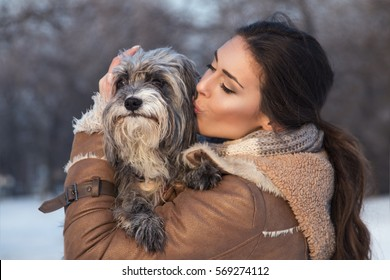 Beautiful girl kissing her dog in nature, outdoors