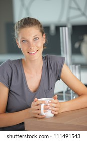 Beautiful girl in kitchen with a cup of cofee or tea