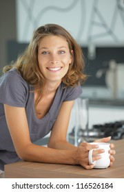 Beautiful girl in kitchen with a cup of coffee or tea