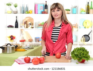 Beautiful girl in kitchen while cooking
