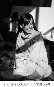 Beautiful girl laughs drinks coffee, tea