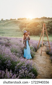 beautiful girl in lavender field is happy with a bouquet of flowers