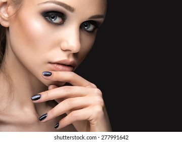 """Beautiful girl in leather jacket with bright makeup and manicure """"Cat's Eye"""". Beauty face. Nail Design. Picture taken in the studio on a black background."""
