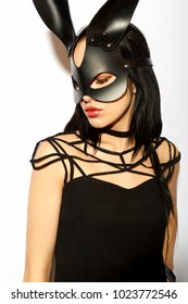 Beautiful girl in a leather mask. Beautiful girl in a little black dress and leather mask. Concept for party