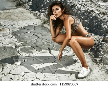 beautiful girl in leopard bikini in hot desert. On the dry ground cracks and beautiful texture. Model with different emotions on her face. Beautiful long legs wearing white sneakers.
